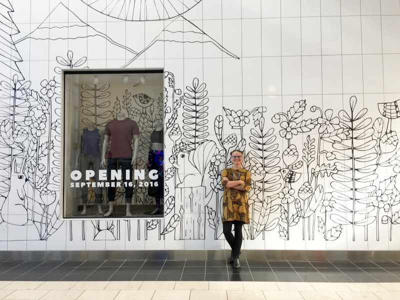 Lisa standing in front of store design she did for the Lululemon shop at Washington Square Mall.